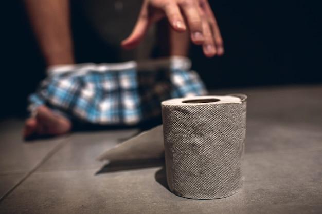 Ręka mężczyzny sięgająca do rolki papieru po wypróżnieniu