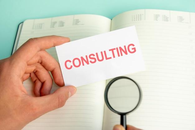 Ręka mężczyzny trzyma białą kartkę z tekstem consulting nad otwartym papierowym notatnikiem i lupą w czarnej ramce, koncepcja biznesowa