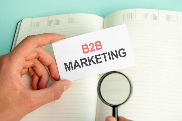 Ręka mężczyzny trzyma białą kartkę z tekstem marketing b2b nad otwartym papierowym notatnikiem i lupą w czarnej ramce, koncepcja biznesowa