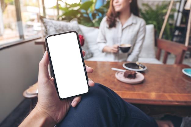 Ręka mężczyzny trzyma czarny telefon komórkowy z pustym białym ekranem z kobietą siedzącą w kawiarni