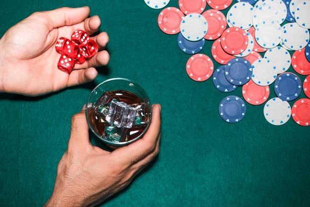Ręka mężczyzny trzyma czerwone kostki i szkła whisky nad stołem do pokera