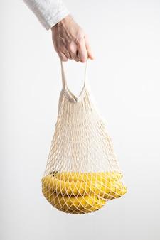 Ręka mężczyzny trzyma ekologiczną torbę z dojrzałymi bananami