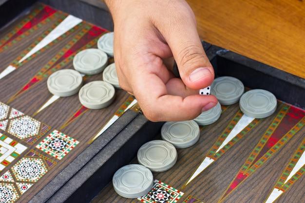 Ręka mężczyzny trzyma grę backgammon
