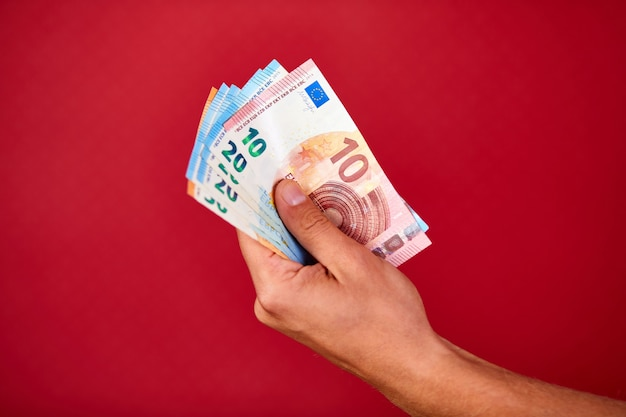 Ręka mężczyzny trzyma i pokazuje banknot unii europejskiej pieniądze euro na białym tle na czerwonym tle, kryty, wyśmienity, kopia przestrzeń