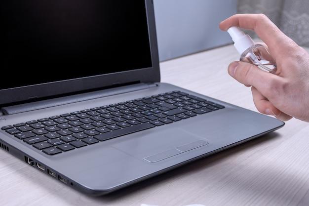 Ręka mężczyzny trzyma i strzela sprayem dezynfekującym i dezynfekuje laptopa, komputer do dezynfekcji różnych powierzchni, które dotykają ludzi. antybakteryjny antyseptyczny żel do rąk