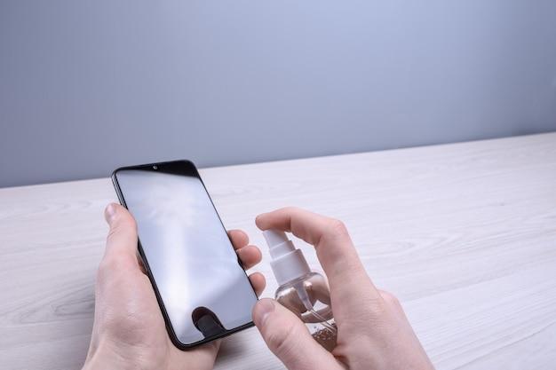 Ręka mężczyzny trzyma i zatrzaskuje spray dezynfekujący i dezynfekuje telefon, aby zdezynfekować różne powierzchnie, których ludzie dotykają