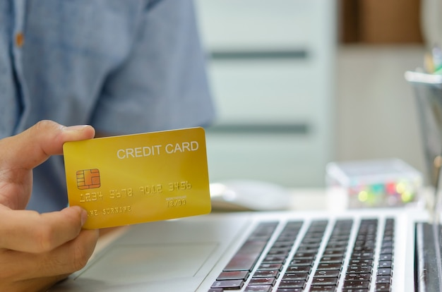 Ręka mężczyzny trzyma kartę kredytową do transakcji online lub zakupów online. złóż wniosek o kartę kredytową, zaciągnij pożyczkę finansową
