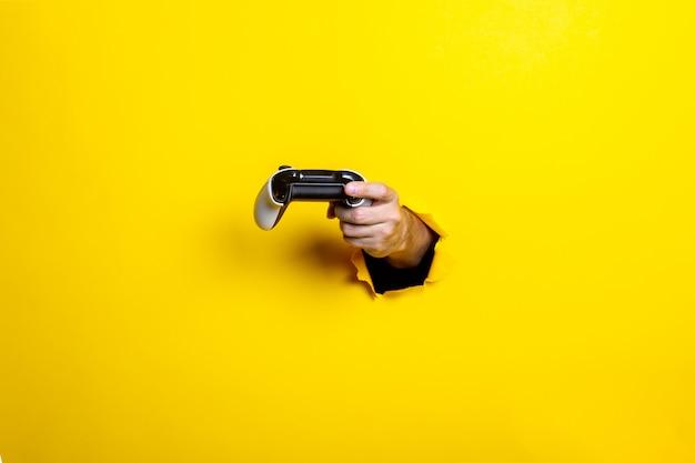 Ręka mężczyzny trzyma kij na jasnożółtym tle
