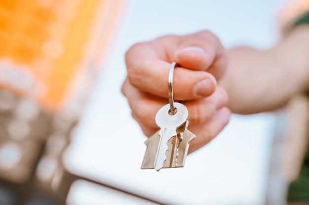 Ręka mężczyzny trzyma klucze do nowego domu na tle wieżowców