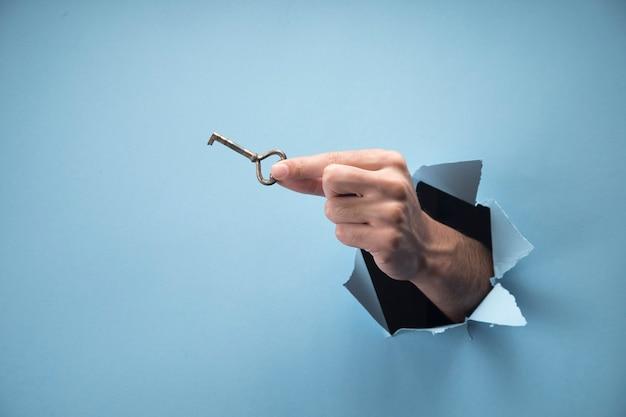 Ręka mężczyzny trzyma klucze na niebieskiej scenie
