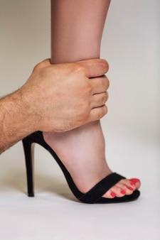 Ręka mężczyzny trzyma kobiecą nogę. złożony związek w parze. szare tło. zbliżenie. pionowy.