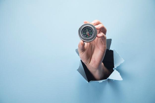 Ręka mężczyzny trzyma kompas na niebieskiej scenie