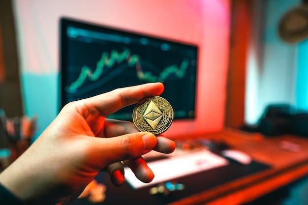 Ręka mężczyzny trzyma monetę eteru przy stole komputerowym.inwestycja