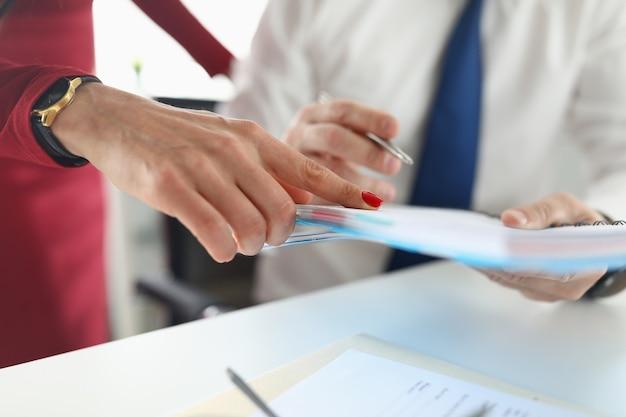 Ręka mężczyzny trzyma notatnik z piórem obok kobiety stoi i wskazuje palcem.