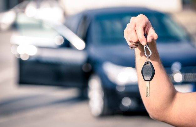 Ręka mężczyzny trzyma nowoczesne kluczyki do samochodu gotowe do wynajęcia