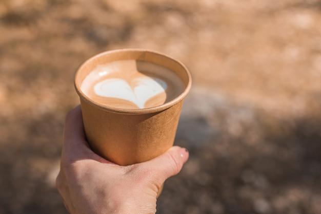Ręka mężczyzny trzyma papierową filiżankę kawy