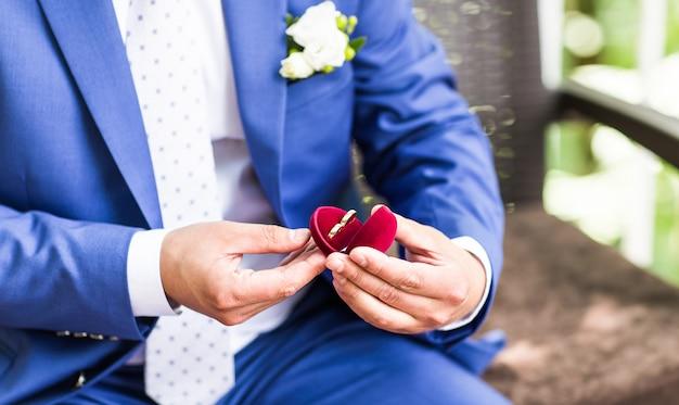 Ręka mężczyzny trzyma pierścionek zaręczynowy
