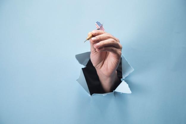 Ręka mężczyzny trzyma rzutkę na niebieskiej scenie