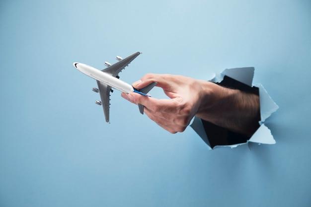 Ręka mężczyzny trzyma samolot na niebieskiej scenie
