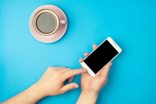 - ręka mężczyzny trzyma smartfon na niebieskim tle i filiżankę kawy. miejsce na tekst