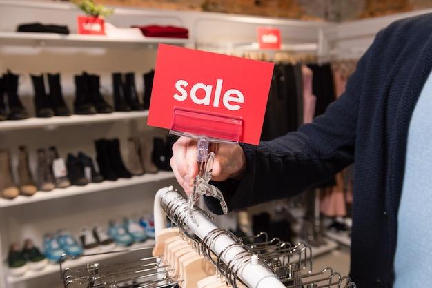 Ręka mężczyzny trzyma sprzedaż czerwoną tabliczkę znamionową
