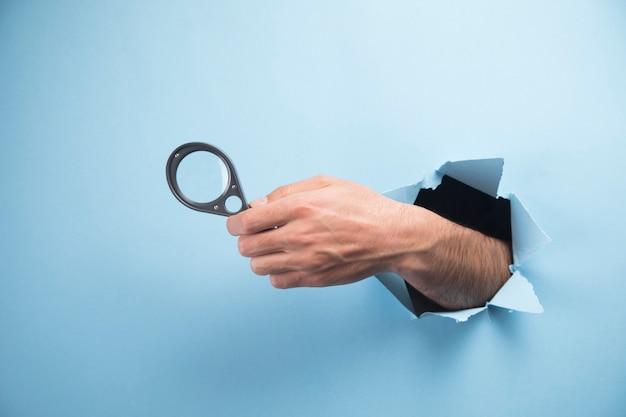 Ręka mężczyzny trzyma szkło powiększające na niebieskiej scenie