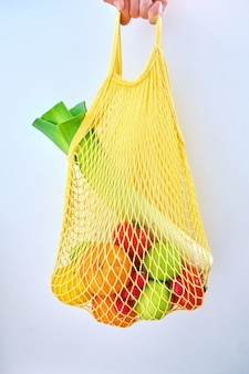 Ręka mężczyzny trzyma żółty worek mieszanych owoców i warzyw