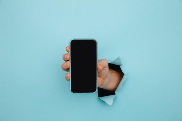 Ręka mężczyzny trzymając smartfon z niebieskiego rozdartego papieru
