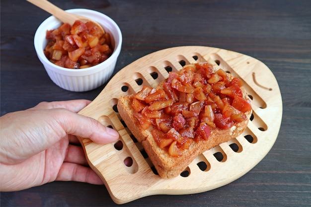 Ręka mężczyzny trzymająca deskę do krojenia chleba domowej roboty tosty z kompotu jabłkowego, umieszczając na czarnym stole