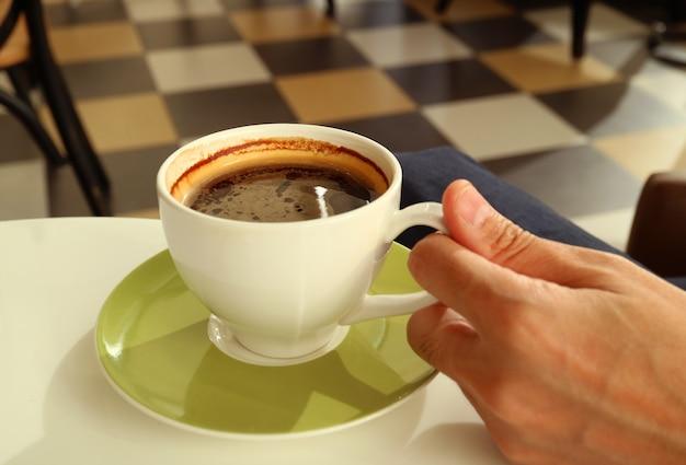 Ręka mężczyzny trzymająca filiżankę gorącej kawy z rozmytym pokojem w tle