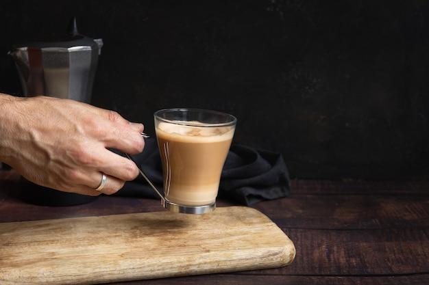 Ręka mężczyzny trzymająca filiżankę kawy z mlekiem na drewnianym stole i włoski dzbanek do kawy w tle