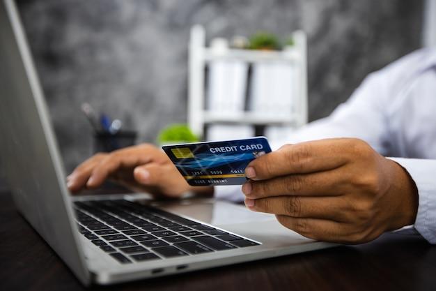 Ręka mężczyzny trzymająca kartę kredytową i próbująca umieścić numer seryjny i hasło na laptopie jako zakupy online, bezpieczeństwo finansowe i ochrona koncepcji e-commerce