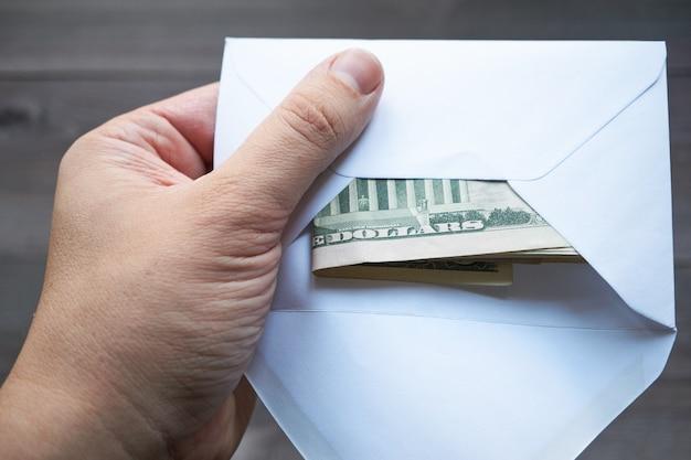 Ręka mężczyzny trzymająca kopertę z oszczędnościami