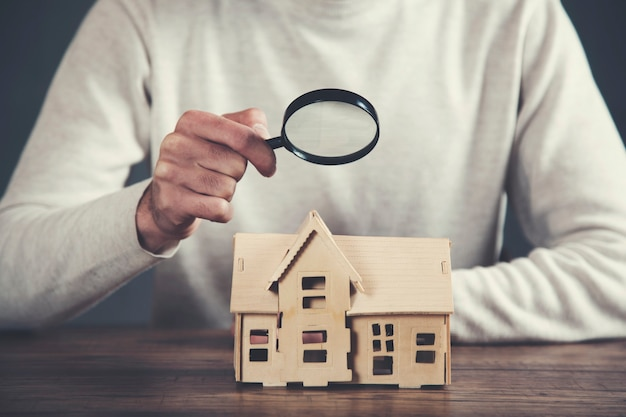 Ręka mężczyzny trzymająca model domu i lupę