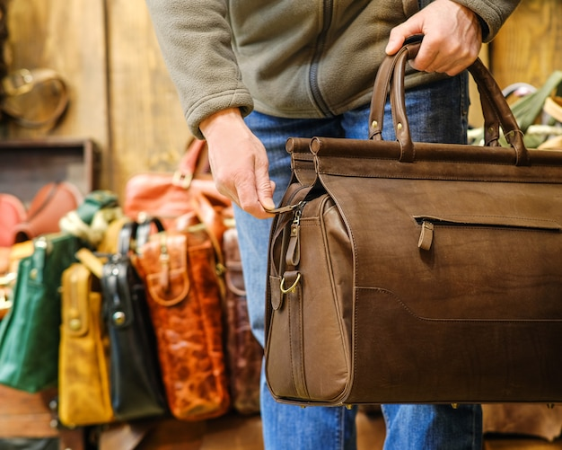 Ręka mężczyzny trzymającego brązową torbę podróżną na tle innych toreb w sklepie. pojęcie produktów ze skóry naturalnej.