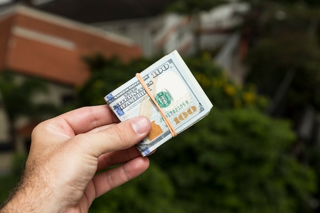 Ręka mężczyzny trzymającego dolary przed krajobrazem miasta