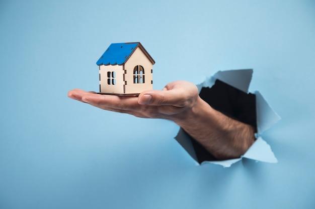 Ręka mężczyzny trzymającego mały dom na niebieskiej scenie