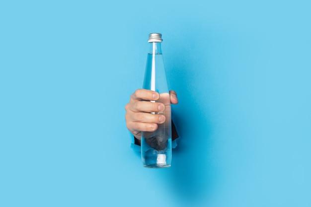 Ręka mężczyzny trzymającego szklaną butelkę wody z zamkniętą pokrywą na niebieskim tle