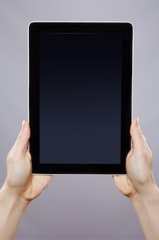 Ręka mężczyzny trzymającego tablet na ścianie, z bliska, koncepcja biznesowa, makieta, aplikacja.