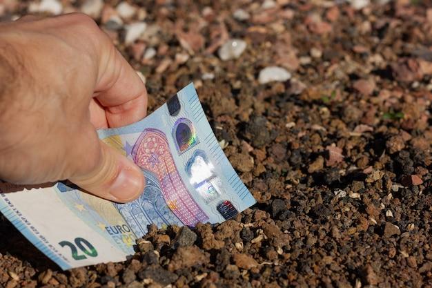 Ręka mężczyzny umieszczająca banknot 20 euro w ziemi gruntowej koncepcja inwestora pieniężnego z nieruchomości