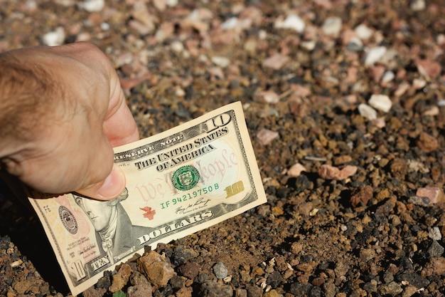 Ręka mężczyzny umieszczająca dziesięciodolarowy banknot w ziemi ziemi koncepcje projektów inwestycyjnych