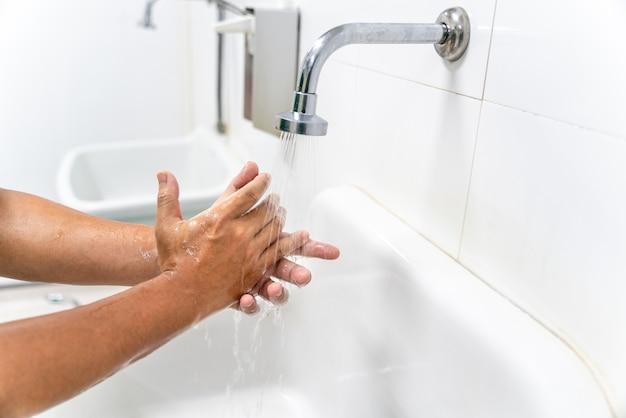 Ręka mężczyzny umyj ręce przy umywalce pianą, oczyść skórę i pozwól, aby woda przepływała przez ręce. zdrowie dla koncepcji profilaktyki covid-19