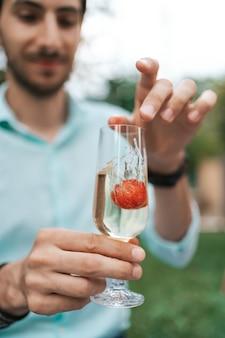 Ręka mężczyzny upuść truskawkę w szklance z winem musującym. piękne życie, święto