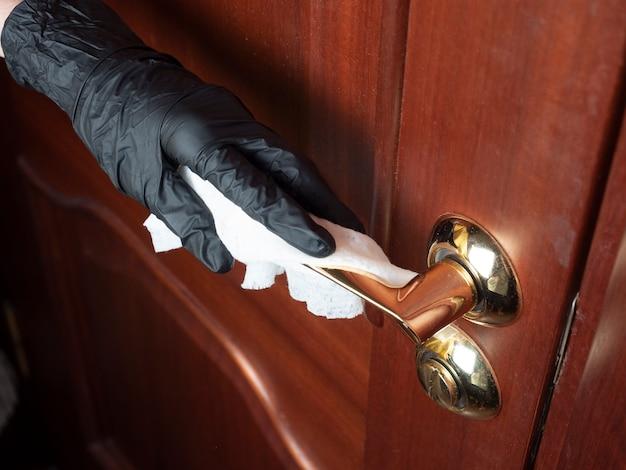 Ręka mężczyzny w czarnej lateksowej rękawiczce wyciera szmatką klamkę frontowych drzwi.