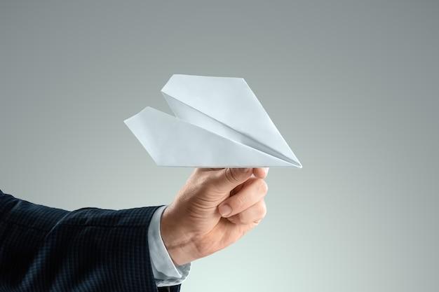 Ręka mężczyzny w garniturze trzyma papierowy samolot. koncepcja uruchomienia, lekki biznes, pierwsze kroki. skopiuj miejsce.