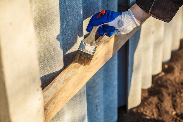 Ręka mężczyzny w niebieskim rękawicy trzyma pędzel malujący lakierem do drewna