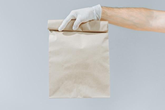 Ręka mężczyzny w rękawicy trzymającej brązową torbę lub torbę do wyjęcia