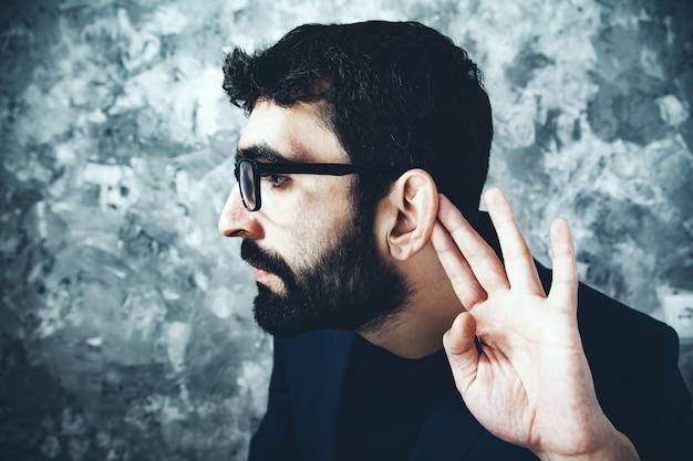 Ręka mężczyzny w uchu na szarym tle