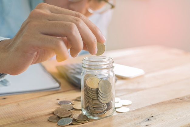 Ręka mężczyzny wkładającego oszczędności do szklanki na drewnianym stole roboczym ze stosem monet, notebooka, smartfona i wykresu - inwestycje, biznes, finanse i bankowość