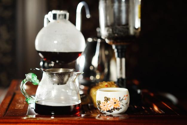Ręka mężczyzny wlewa czarną herbatę do pięknej chińskiej miski na tle stolika herbacianego. herbaciana ceremonia